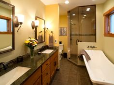 This charming yellow bathroom features a long double vanity with wood cabinets, a contemporary soaking tub, and a spacious walk-in shower.