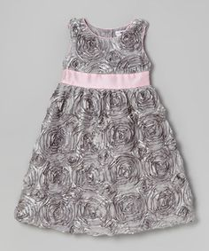 This charming frock will look smartly sweet on any little lady. Complete with a luxurious satin finish, shimmering rosettes and pink trim, this piece is one party-perfect number.