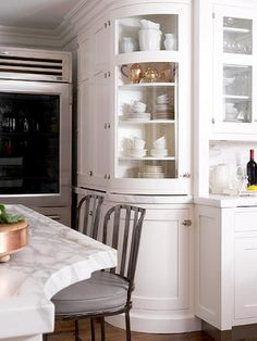 Glass-front cabinets for the kitchen. Love the curved cabinetry and details on the island countertop. My next kitchen.