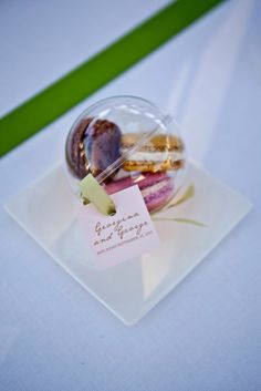 Cadeau invité de mariage: boule de Plexiglas avec 3 macarons Pierre Hermé, ruban de satin vert et petite étiquette personnalisée aux prénoms des mariés. Réalisé par Chez Sandrine Votre wedding planner Mariage dans l'air