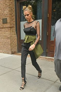 Cara Delevingne in an Alexandre Vauthier haute couture black jumpsuit cinched around the waist with an army green belt tied in an oversize bow.