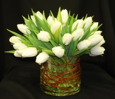 This is a floral arrangement that features white tulips. See our entire selection at www.starflor.com.  To purchase any of our floral selections, as gifts or décor, please call us at 800.520.8999 or visit our e-commerce portal at www.Starbrightnyc.com. This composition of flowers is generally available for same day delivery in New York City (NYC)  LV056