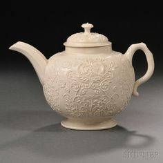 Staffordshire Salt-glazed Stoneware Teapot and Cover, England, c. 1755, globular press-molded with flowers and birds to one side, the reverse with flowers, lg. 8, ht. 5 5/8 in.