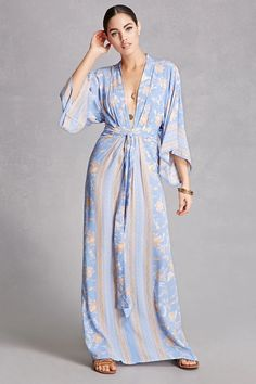 A woven maxi dress by Selfie Leslie™ featuring an allover floral print, striped trim, a plunging neckline, long boxy sleeves, a zipper front, and an attached belt at the waist.