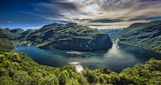 wimvandemeerendonk, back in the cold brrrrr! posted a photo:  The classic shot from Geiranger, on a great day. Only an ultrawide lens can show the grandness of the view and even then you have to stitch the shots to get it all in one image.  Norway, a stunningly beautiful country. Around every corner a chance for a scenic image, forcing me from time to time to stop every kilometer to get out of my car, sometimes with screeching brakes, and sometimes forcing me to curse because there was no…