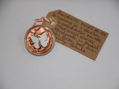Pillsbury's Pieces No. 154.  Pin - pale metallic apricot capsule with white paper butterfly.  Available in exchange for a donation to KAT (Kathmandu Animal Treatment Centre).  AVAILABLE AT St. George's Church Summer Fete, Saturday 13 June from 11.00 - 13.00
