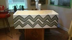 Repurposed old wooden box. Painted white then added gray two toned chervon design. Will be storage in my classroom.