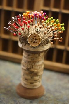 Wooden Spool wrapped with cloth measuring tape and covered in burlap a rainbow of pins = Pincushion Love
