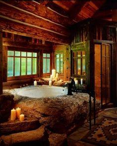 Log home bathroom... tub mounted on stone platform to take advantage of the view.