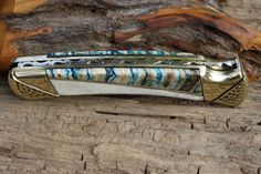 Customized Buck 110 detail of hand filework, carved bolsters with mammoth tooth and camel bone handles