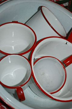 Red rimmed Enamelware. Would love these for hot chocolate on wintry beach, garden