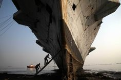Nov. 22, 2014. Workers climb to enter India's first aircraft carrier INS Vikrant to dismantle it at a ship-breaking yard in Mumbai. The iconic naval vessel, purchased from Britain in 1957, played a key role during the India-Pakistan war of 1971 and was decommissioned in 1997.