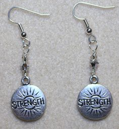 "Handcrafted by Teal Palmetto, LLC. Strength is not just physical, it's also mental.  Show the world your inner and outer strength with these earrings.  The silver-coated pewter ""STRENGTH"" charms are joined with beautiful Swarovski crystal and glass accent beads.  They dangle from silver fish hook ear wires. Price: $15."
