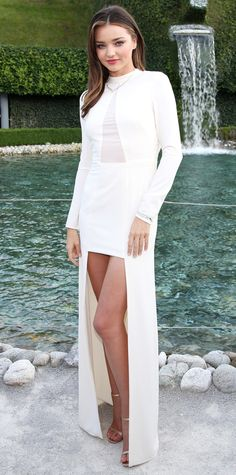 Miranda Kerr arrived at Swarovski's collection launch event in Austria in a cream-colored Halston Heritage column with a high-low hem and illusion neckline. To complete the look, Kerr piled on dreamy diamond jewelry and rose-gold Jimmy Choo heels.