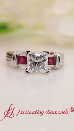 This 3 stone moissanite engagement ring marvelously displays a stunning princess cut moissanite in the center complemented by a dazzling princess cut ruby placed on either side of the center stone along with a double bar design adding grace and opulence to the ring. #fascinatingdiamonds #moissanitering #engagementring #platinumring #ring #3stonering #ruby #moissanite #princesscutmoissanite Trinity Ring, 3 Stone Engagement Rings, Best Diamond, Three Stone Rings, Platinum Ring, Moissanite Rings, Princess Cut, Bar, Jewelry