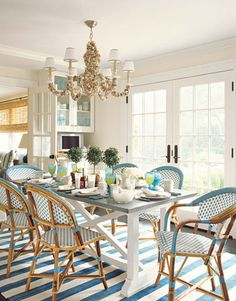 "Whittaker added shades to the shell chandelier from Mecox Gardens. French café chairs from TK Collections. The blue and white Stark rug ""creates continuity between kitchen and sitting room, and breaks up a large expanse of floor."""