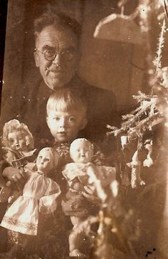 Vintage Photo:  An old man & a little boy holding 3 dolls beside a Christmas tree.  Could this possibly have been a progressive family during that time period who did not believe in forcing children to comply with strict gender roles?  If so, good for them!