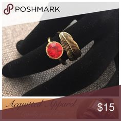 Birds of A Feather Ruby Red Ring Ruby red stone accentuates a wrapping feather in antiqued gold. Perfect for love or luck.  Brought to you as part of the Acquitted Apparel Boutique Jewelry Line! Acquitted Apparel Jewelry Rings