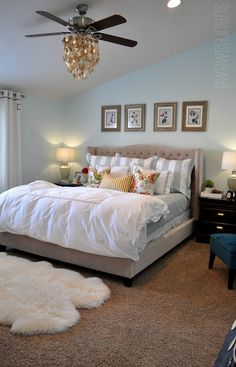 master bedroom with pale blue walls and tufted headboard. Capiz shell chandelier.