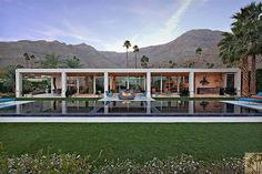 This sleek Desert Modern in California has a white shell, covered patios, walls of glass, colorful outdoor furniture, a fire put, large pool, and manicured lawn.