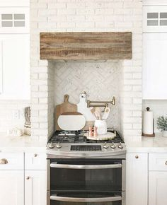 Kitchen brick hood and kitchen brick backsplash. Using distressed painted brick in kitchens is a trend that is here to stay. I love that Nina chose to use the painted brick in a herringbone pattern behind the stove. Rustic Kitchen Decor, Kitchen Redo, Home Decor Kitchen, Kitchen Interior, New Kitchen, Home Kitchens, Kitchen Remodel, Kitchen Design, Kitchen Brick