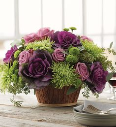 It is filled with lavender roses, mums and flowering kale.