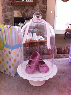 pink glitter baby shoes in cloche on gift table