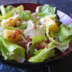 "Tropical Salad with Pineapple Vinaigrette - ""An easy salad to make with a bag of salad greens, pineapple, bacon bits, nuts and toasted coconut. Use fresh pineapple, if you can, and substitute toasted almonds for the macadamia nuts, if desired."" —"