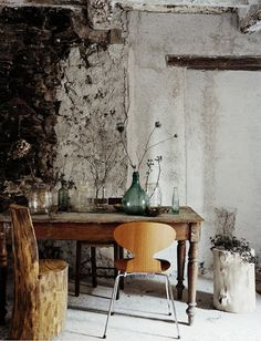 Beautifully weathered wall, hand made log chair paired with Arne Jacobsen Ant Chair, interesting collection of glass bottles and vessels #diningtable #diningroom #antchair