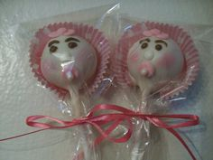 Cake pops dipped in white chocolate then placed in mini cupcake liner for bonnets.  Made pacifiers out of fondant and attached a sugar pearl with melted choc and made bows of fondant.  Used melted choc for eyes, eyebrows, nose and to attach pacifier and bows.  Used color dust to put color on for cheeks.