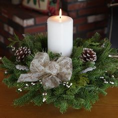 Winter Elegance Pillar Candle Centerpiece with a large white bow and frosted pine cones. Perfect for a round table.