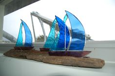 copper foiled boats on driftwood