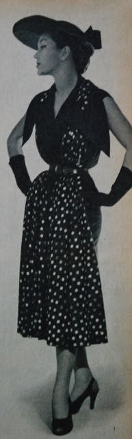 slim black dress with large collar through which a polkadot stole is draped, Libelle 1951
