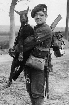 Soldier of the Royal Scots Regiment holding a black goat kid