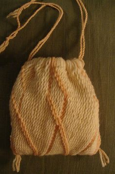 "Made in advance, ""a lovely piece that looks like a dreamsicle, in cream and peach wool, with the twined patterned detail around the main sprang body of the bag.""--Made for the 2008 Maryland Sheep and Wool Festival Sprang Demo"