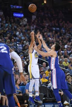 Stephen Curry of the Golden State Warriors shoots over Dario Saric of the Philadelphia 76ers during an NBA basketball game at ORACLE Arena on...