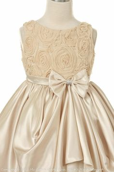 Gorgeous champagne colored dress with a small bow in the center with ruffles and a floral design on top. Chic, adorable, and vintage if leaning towards that style for your flower girl (s)
