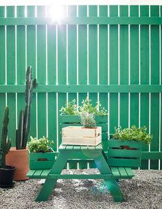 Cageots en bois remplis de plantes en pots et posés sur une table de pique-nique verte.