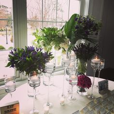 """Place card table with grouping of white parrot tulips purple lisianthus blue Veronica purple """"Shogun"""" roses and purple Dutch clematis accented with floating candles. #floraldesign #eventdesign #flowershop #bridalflowers #weddingdecor #weddingdecor #florist #flowers #dvflora by petalsfloraldesign"""