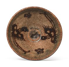 JIZHOU' 'PAPERCUT' 'PHOENIX' BOWL, SOUTHERN SONG DYNASTY, with rounded sides supported on a low foot and rising to a vertically lipped rim, decorated in papercut resist with a pair of long-tailed phoenix and three prunus blooms in dark-brown, all reserved against a ground dappled in caramel brown, the exterior covered in a rich brown glaze stopping neatly above the buff stoneware body. D 4 in.