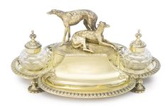 A Victorian Silver-gilt Inkstand, Robert Garrard II, London, 1874, of quatrefoil form on four leafy supports, the raised central compartment with hinged cover surmounted by reclining and standing greyhounds.