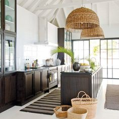Dark wood, light walls, and natural elements, from the woven lighting to the handy baskets, make this coastal kitchen a breath of fresh air. Bringing in simple, earthy accents is an easy way to bring a natural palette into your home.