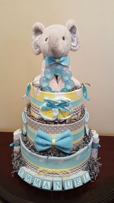 Adorable blue, grey, and yellow elephant diaper cake.  Baby shower centerpiece gift.  Love the name blocks. check out my Facebook page Simply Showers for more pics and orders.