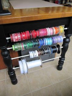 Use tension rods between the table legs in your craft room for ribbon storage or wrapping paper storage!