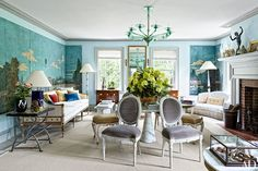 The living room decor is centered on a circa-1930 Italian green-glass chandelier and an Angelo Mangiarotti marble pedestal table encircled by 18th-century Swedish side chairs; at far left, a Gustavian sofa upholstered in a Colefax and Fowler linen-cotton is paired with 19th-century scenic wallpaper panels by the Velay Manufactory.