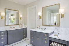 Gray and gold bathroom features separate his and hers gray washstands adorned with campaign hardware paired with white marble countertops and backsplash under gold and black mirrors illuminated by Refined Rib Sconces.