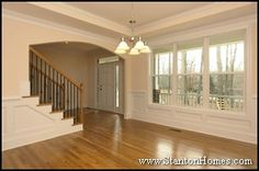 Dining room with wainscoting, trey ceiling, triple windows, and arched opening to foyer. Beautiful hardwood floors.