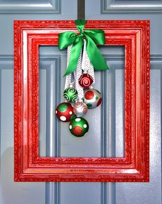 Holiday wreath with a picture frame, ribbon, and a few ornaments.