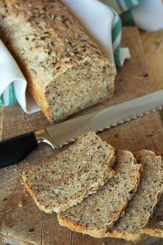 Cinco Quartos de Laranja: Pão de sementes Ingredientes: 250 g de farinha integral 250 g de farinha de trigo 1 saqueta (4,6 g) de fermento em pó 1 colher de chá mal cheia de sal 15 g de açúcar amarelo 1 dl de leite 2,5 dl de água morna 40 g de sementes de girassol 40 g de sementes de linhaça castanhas Farinha de trigo para polvilhar Água para pincelar Sementes de girassol e de linhaça para polvilhar