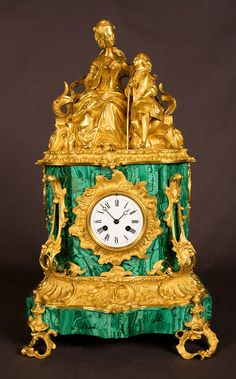 Mantel Clock in Green Malachite and Ormolu Ornaments with a Lady and her Son Dressed in 18th century Costume at Serge Daelmans Antiques and Fine Art, in , Belgium.